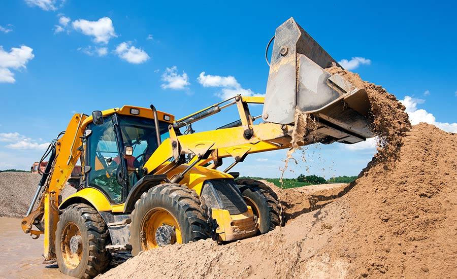 Baggermaschine entlädt Sand während der Erdarbeiten