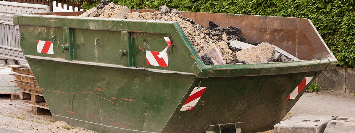 Ein grüner Container mit Bauschutt vor einer grünen Hecke