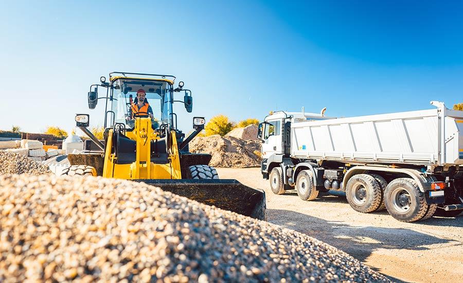 Bauarbeiter bei Erdarbeiten mit Radlader und Bauschutt LKW